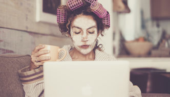 portrait of woman working from home wearing rollers and facial